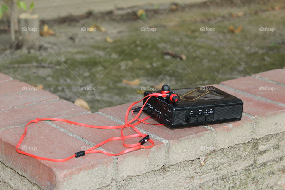 cassette player sitting on a red brick wall on a sidewalk in Sacramento California