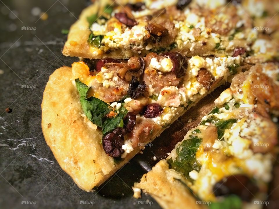 Delicious Mediterranean Pizza featuring Feta Cheese, Spinach, Sausage, Olives, Garlic, Mushrooms and Olive Oil.
