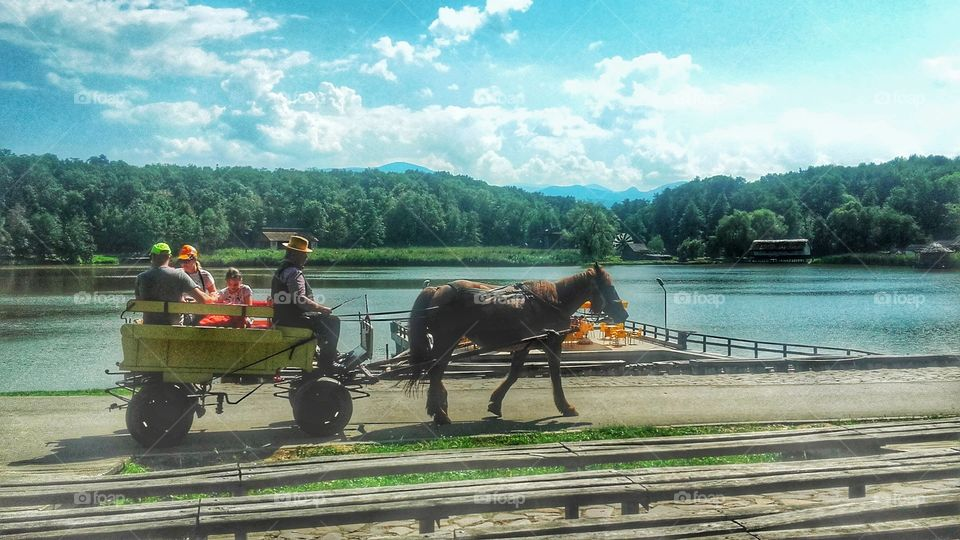 At the Village Museum in Sibiu - people are going for a ride in a horse drawn cart.