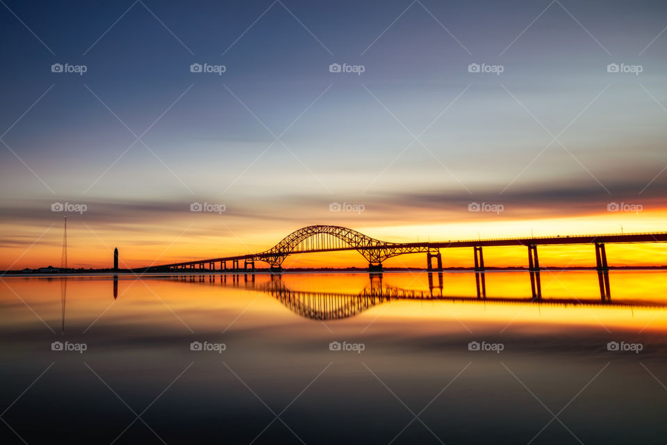Silhouette of a long arched bridge stretching across a calm body of water at sunset. Clouds and bridge reflected perfectly in the water