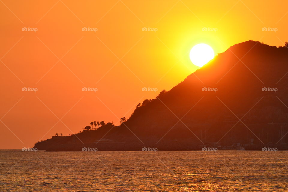 Silhouette of mountain near sea during sunset
