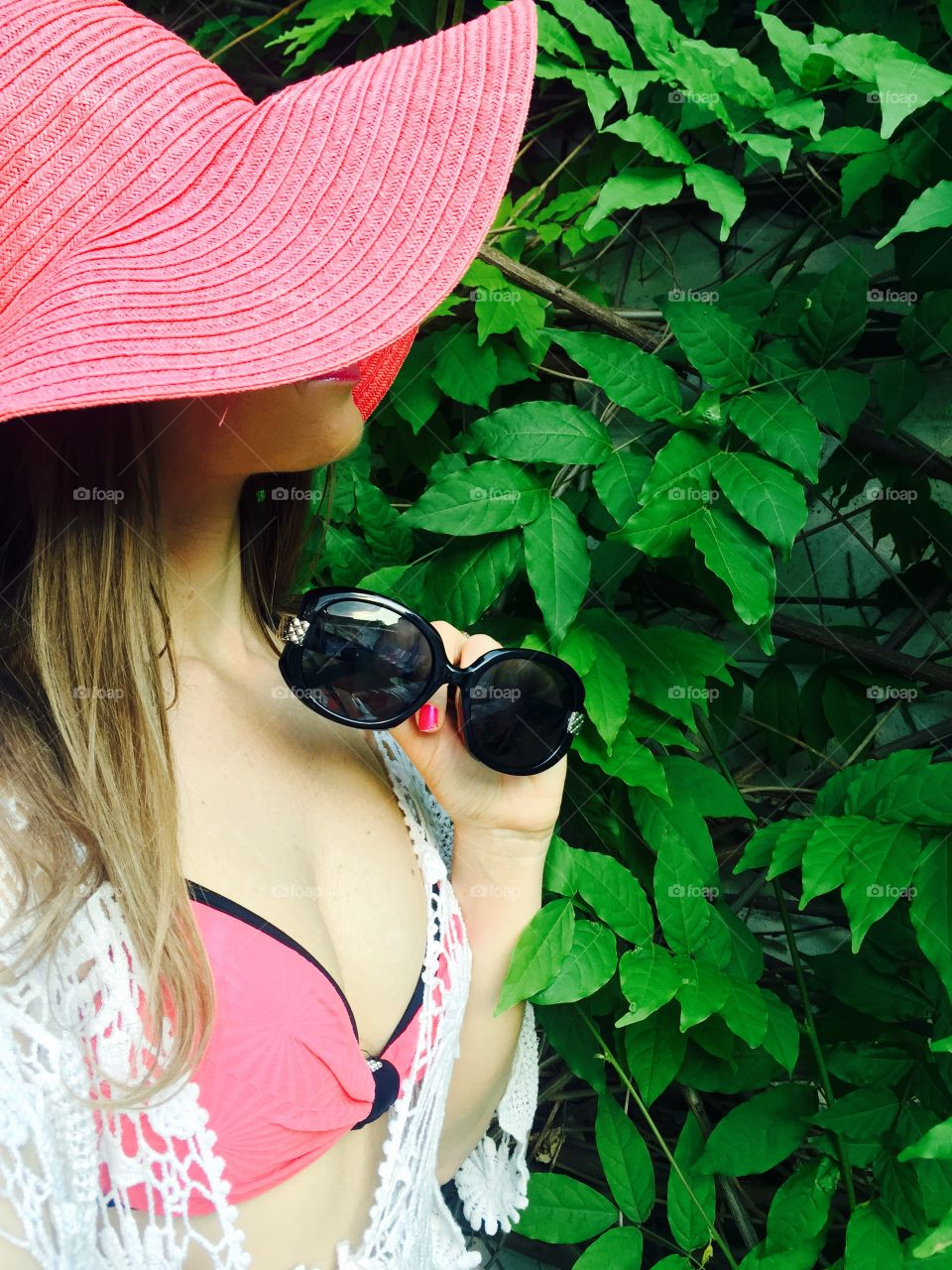 Selfie of woman with long dark blonde hair with black sunglasses in her hand standing against background made of leaves