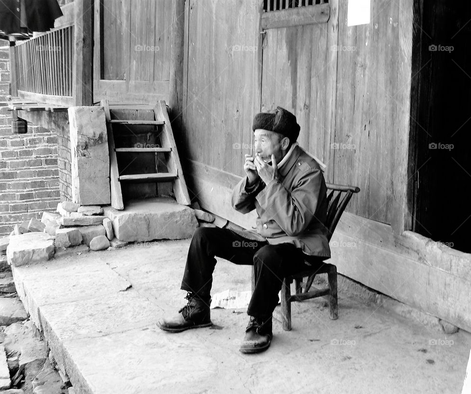 Elderly villager making beautiful tunes with his harmonica outside his home.