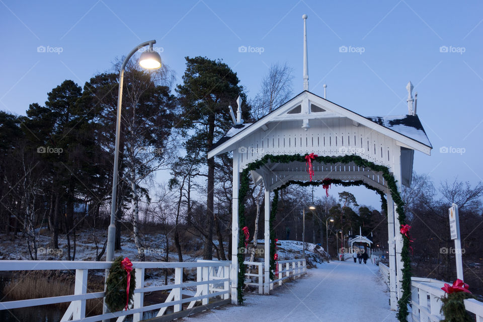 HELSINKI, FINLAND - DECEMBER 27: Old and historical wooden bridge from Seurasaari outdoors museum island towards mainland Helsinki decorated for Christmas decoration on cold evening December 27, 2015 in Helsinki, Finland.