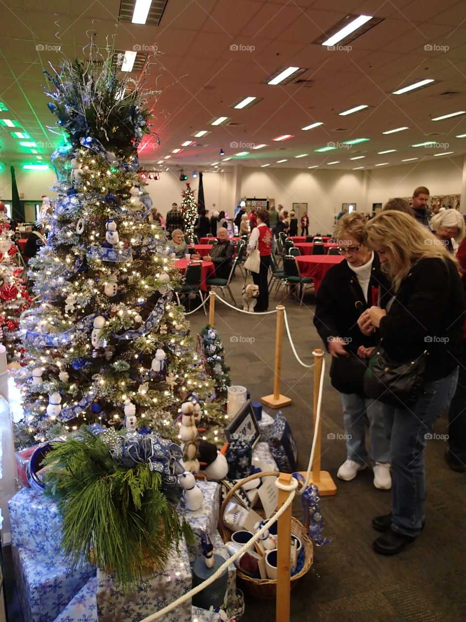 People looking at one of the many beautifully decorated Christmas trees at a fundraising event.