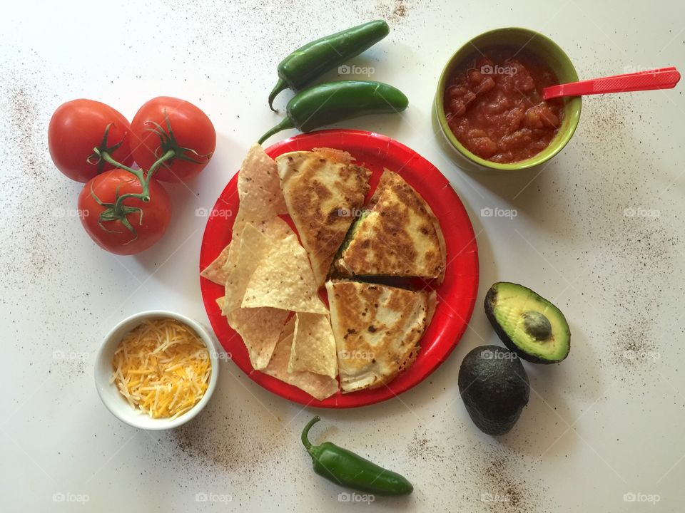 Delicious homemade quesadilla with tortilla chips, accompanied by ingredients.