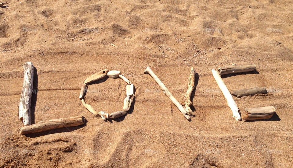 Love written with driftwood on the beach