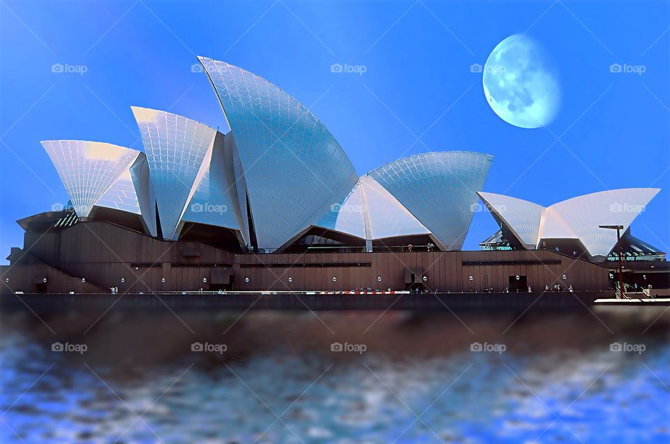 An early evening moon rises over Sydney Opera House.