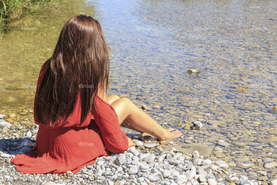 Rear view of a woman sitting at lake side