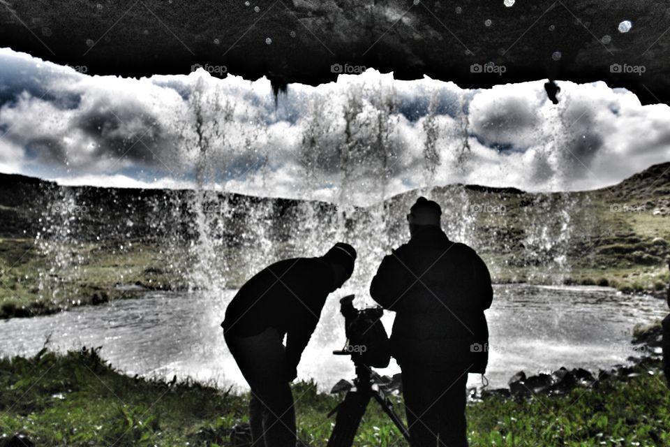 Filming from behind a waterfall in Ethiopia . Standing behind waterfall underneath overhang