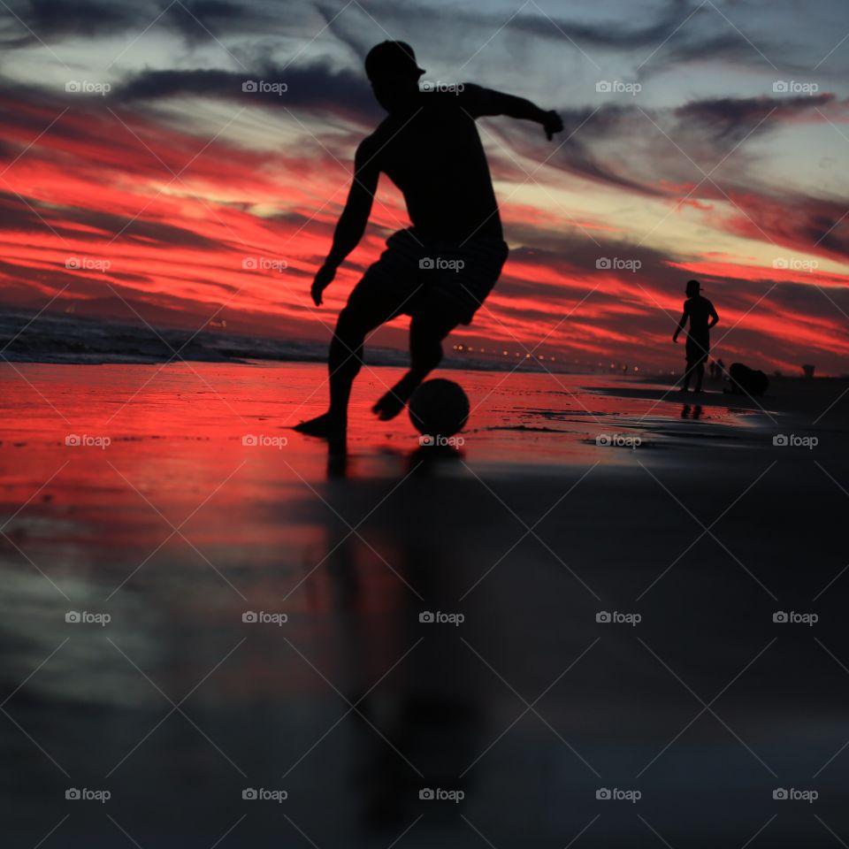 Man playing soccer at beach