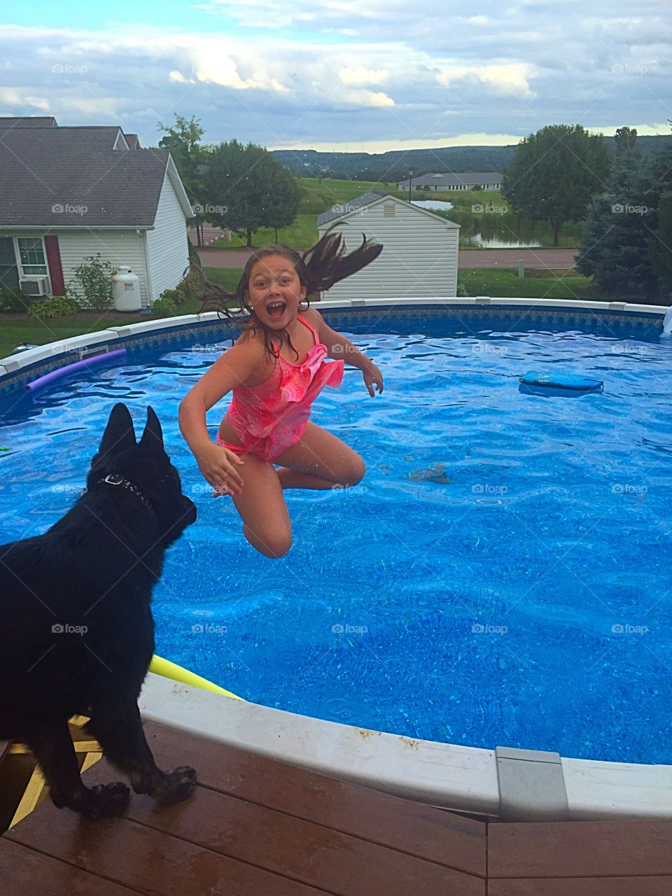 Girl with dog at pool side