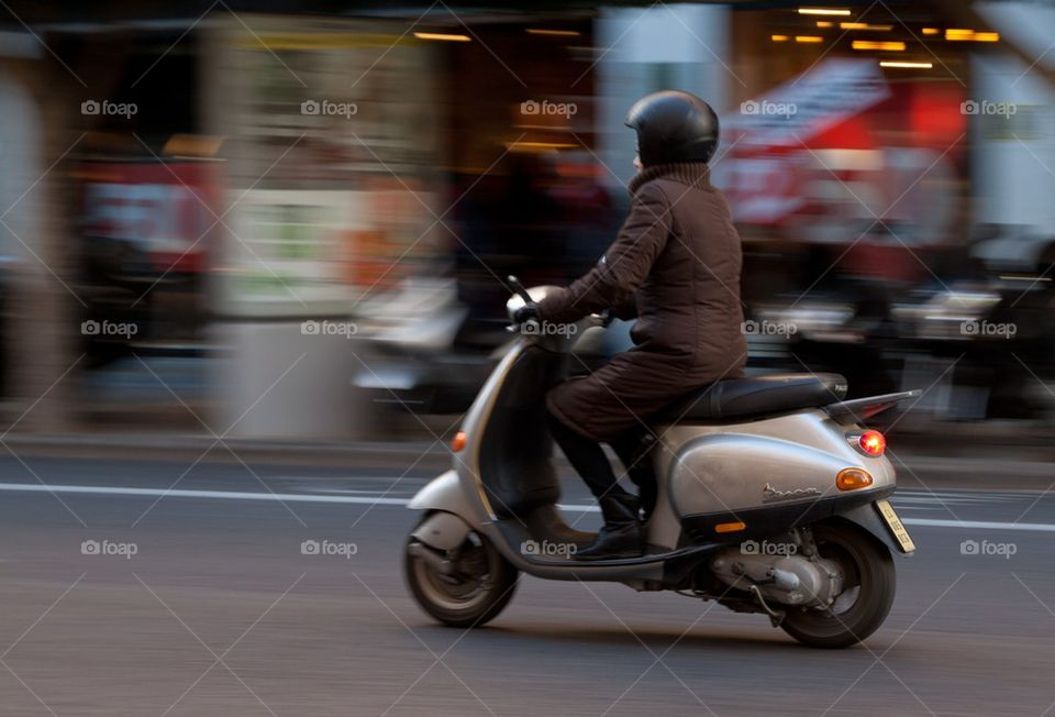 Woman on Vespa scooter.