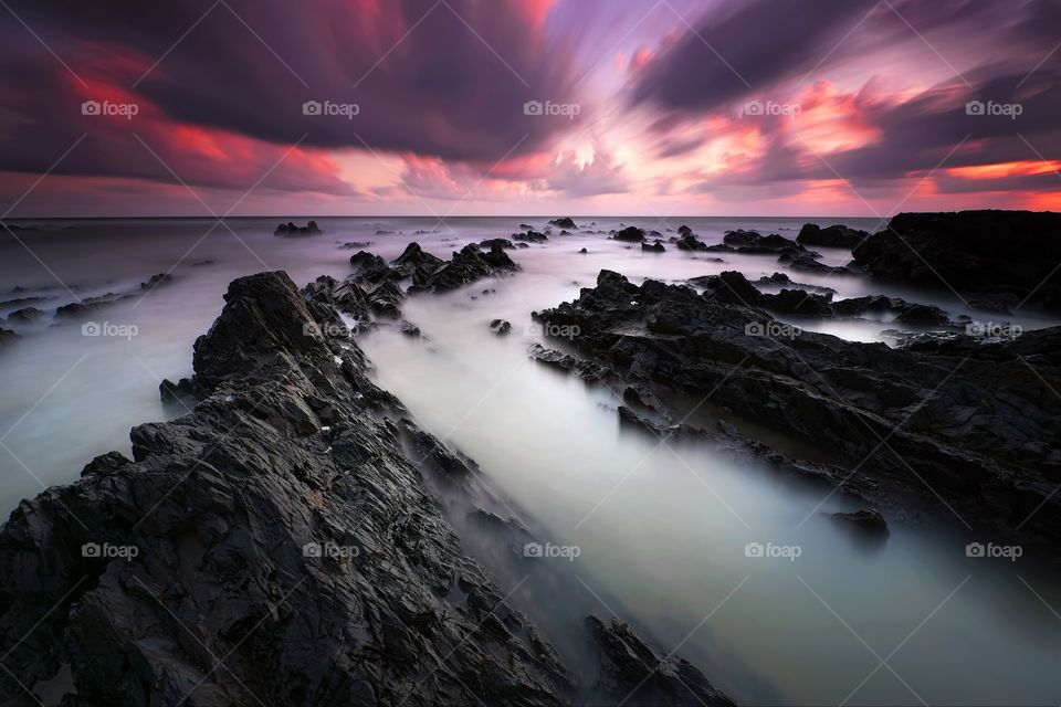 Long exposure seascape with sunset background and dramatic sky