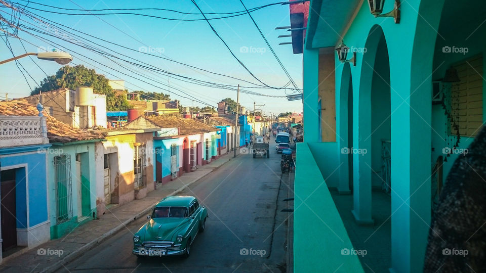 Colorful Houses and Old Cars in Cuba. A 1950s American car makes its way down the street in Trinidad, Cuba.