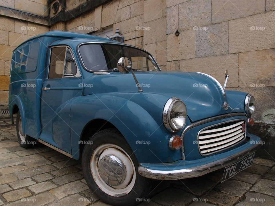 A vintage blue delivery car parked on stone on the exterior of Howard's Castle outside of York in England on a summer day.