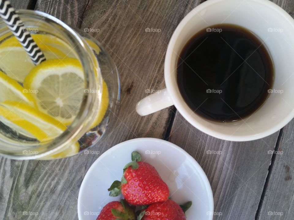 Black coffee with lemon water and strawberries