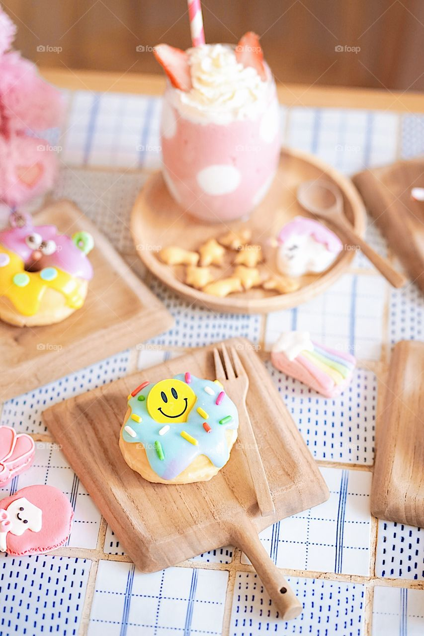 Cute donuts. Cute sugar glazed doughnut with happy smiling face and a cute monster doughnut served on a wooden table with a pink polka dot milkshake. Creative idea for fun birthday or private party.