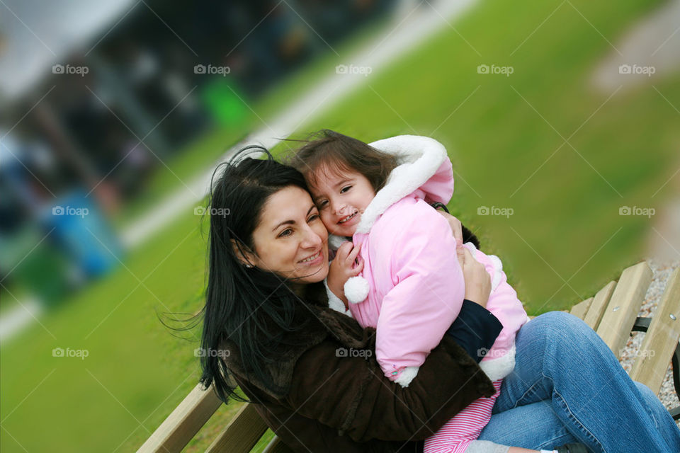 diverse mom and daughter sitting in the bench