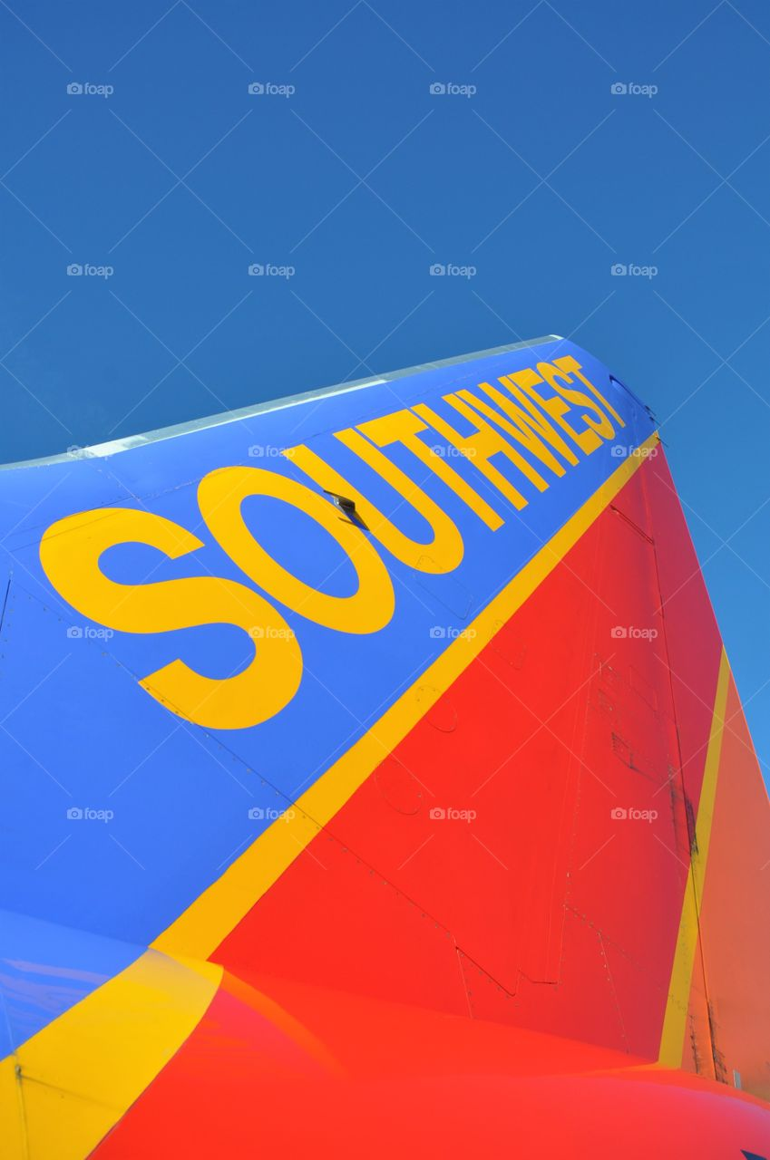 Southwest Airlines tail section rises into a bright blue sky.