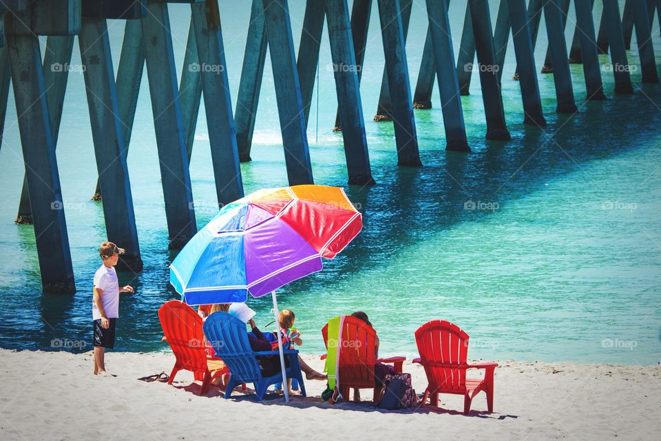 Colorful umbrella and chairs with family on Florida beach near a pier. Rainbow umbrella on a Florida beach with family on vacation