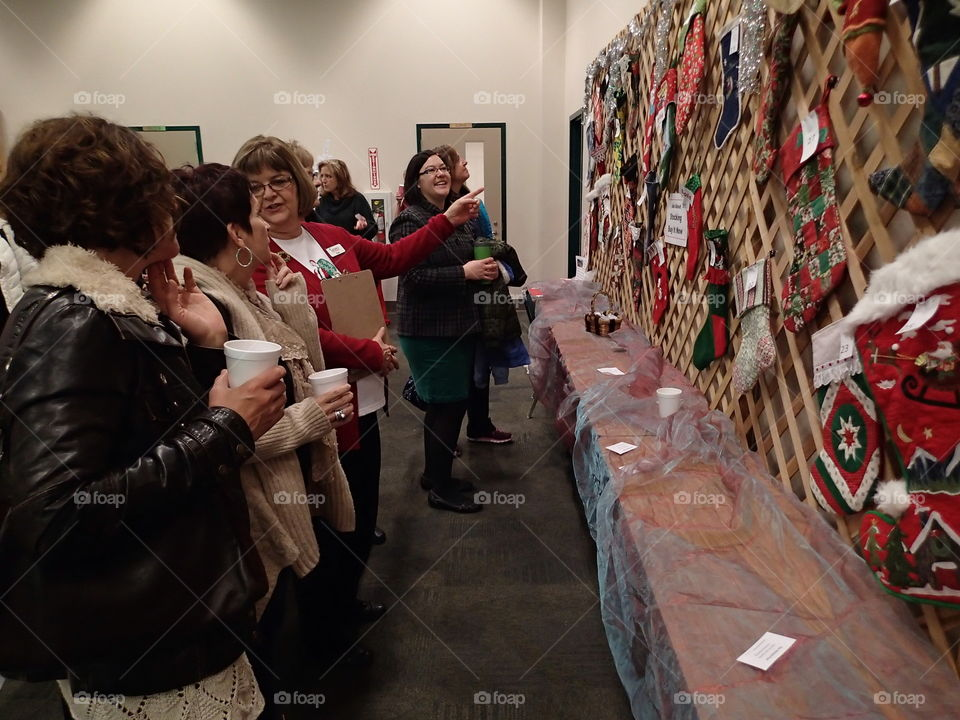 A crowd gathers at a holiday bazaar to view Christmas ornaments hanging on a wall.