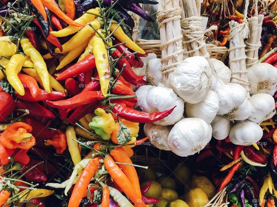 Yellow, red and orange chili peppers and garlic on sale