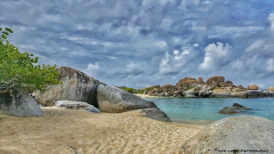 Boulders on sandy beach at coastline
