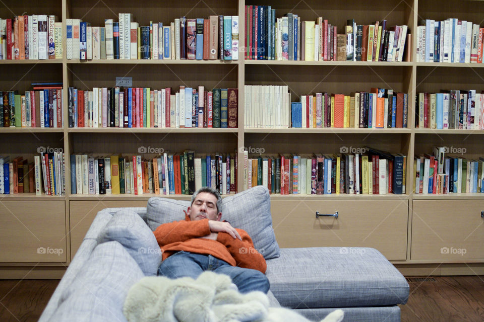 Man sleeping on a couch in front of a bookshelf