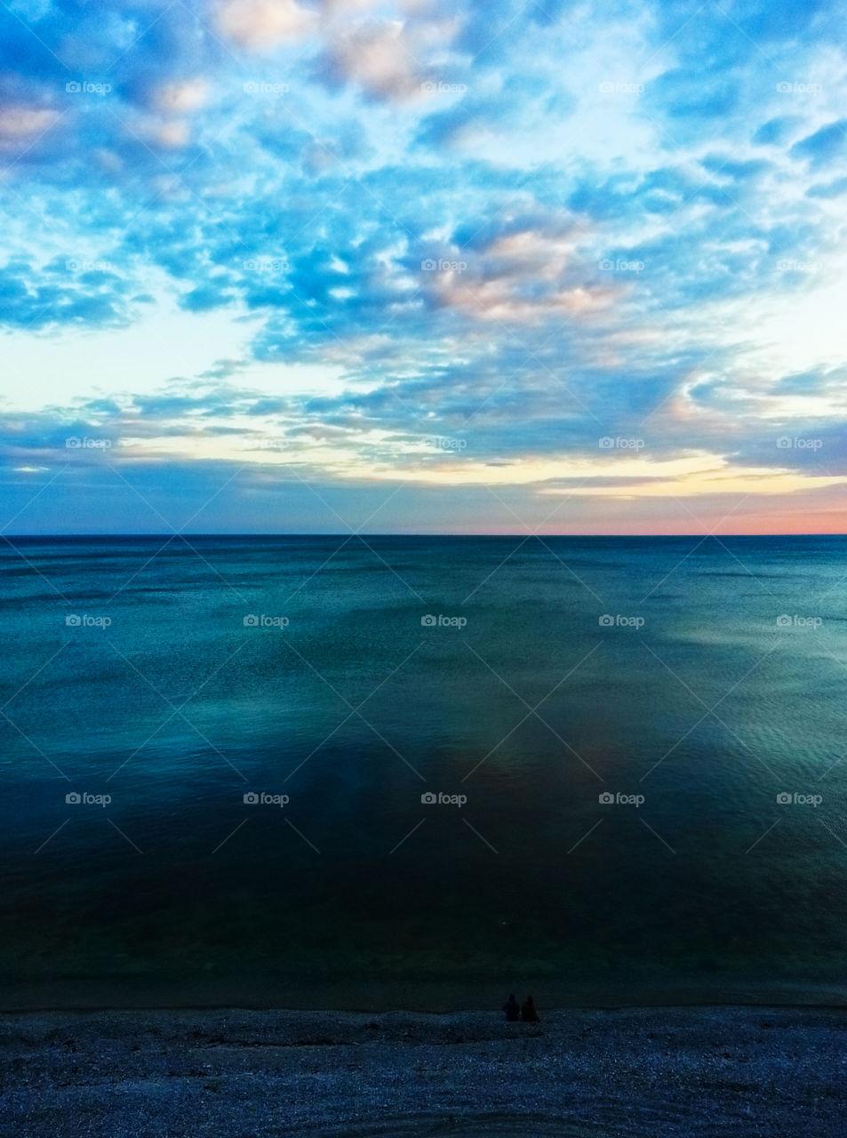 Couple meeting dramatic sunset near ocean