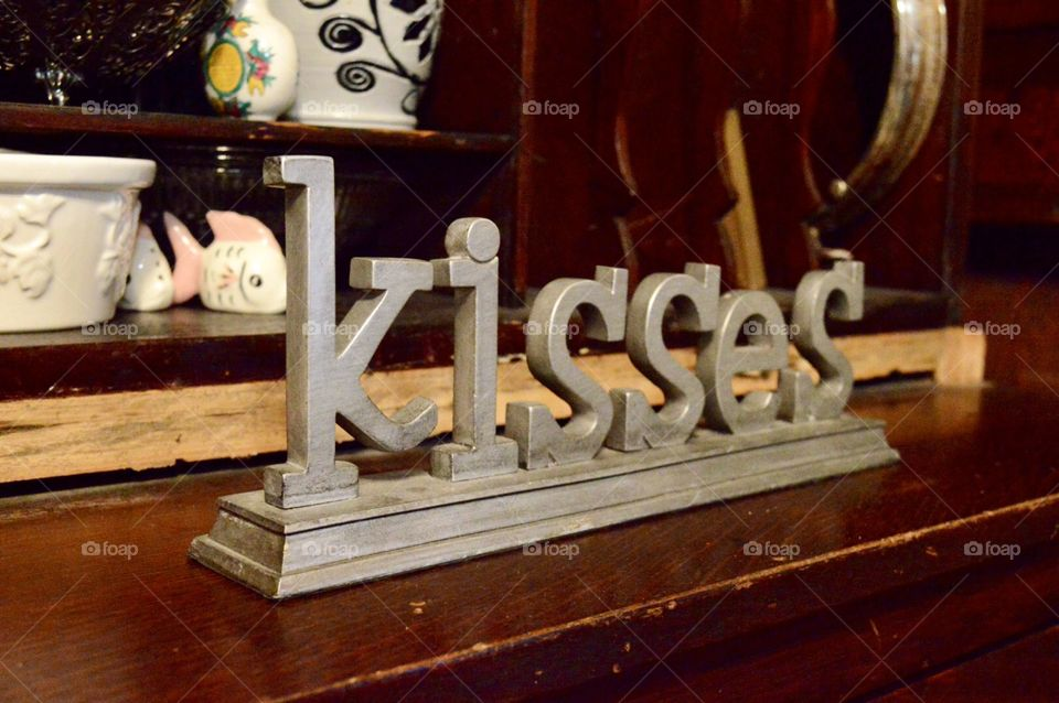 Gray metal Kisses word on a piece of wooden furniture