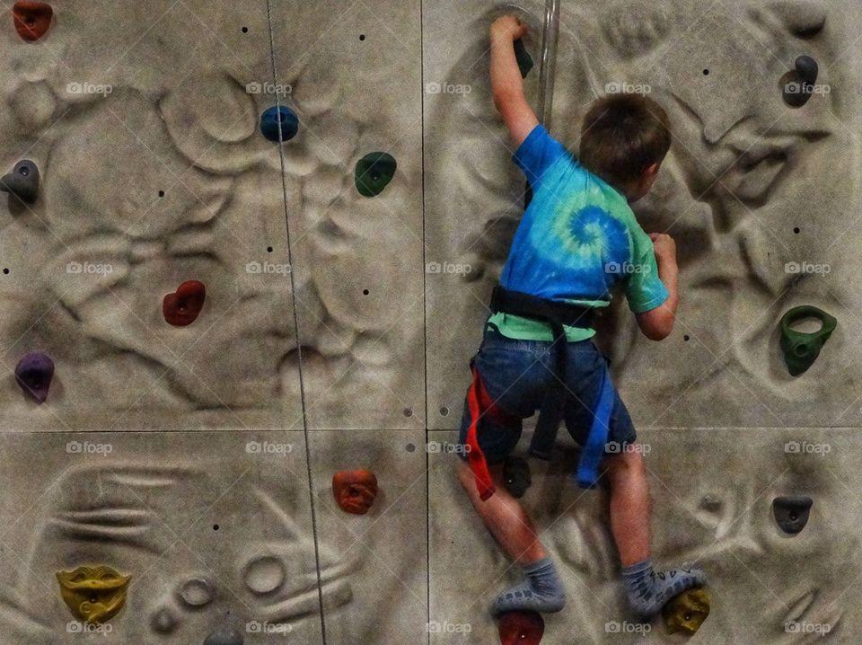 Young Boy Climbing A Rock Wall. Boy In Harness Scaling A Wall