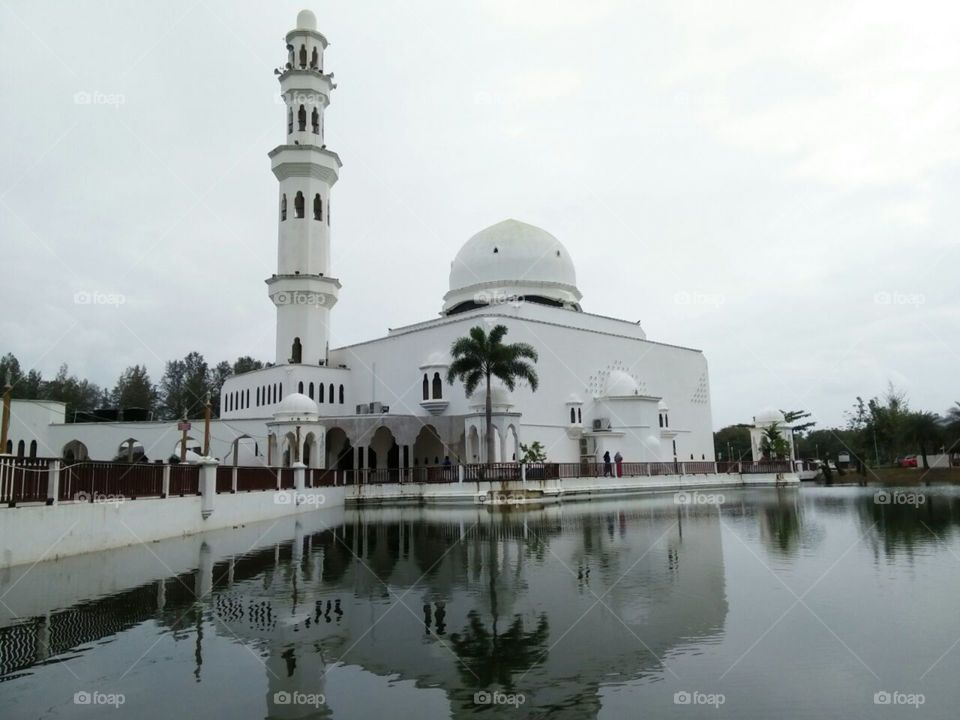 White floating mosque at terengganu malaysia..reflection on lake visible by necromacy