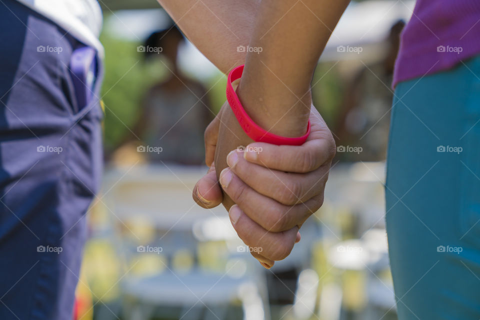 Close-up of two people holding hands