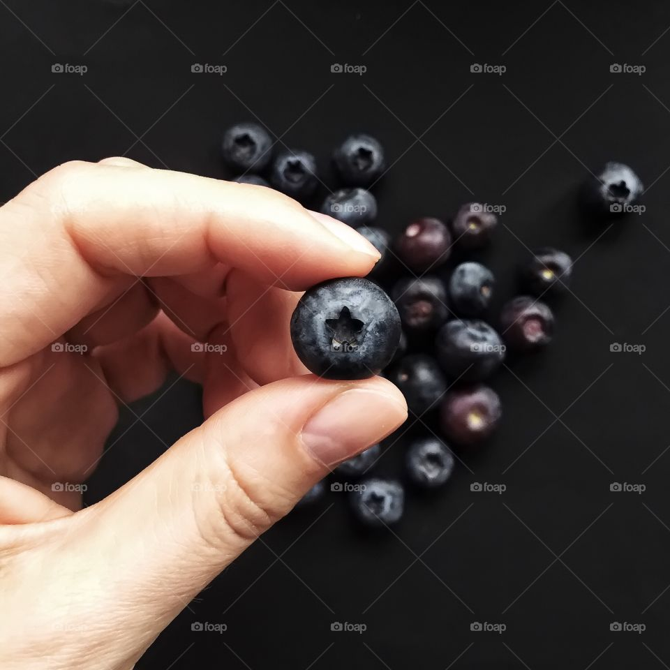 Woman hand holding blueberry