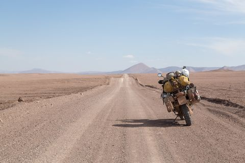 Desert view with motorcycle. Atacama desert road view with motorcycle parked on the right side. Dry gravel road leading towards hills. Adventure bike