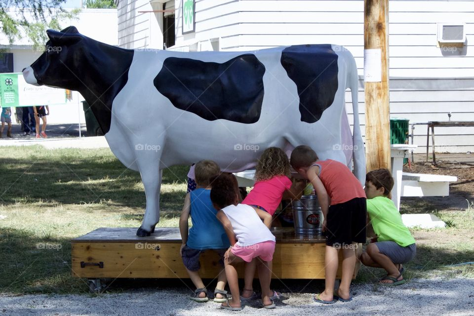 Little children, excited about learning how to milk a cow, take turns practicing on a dairy cow milking simulator