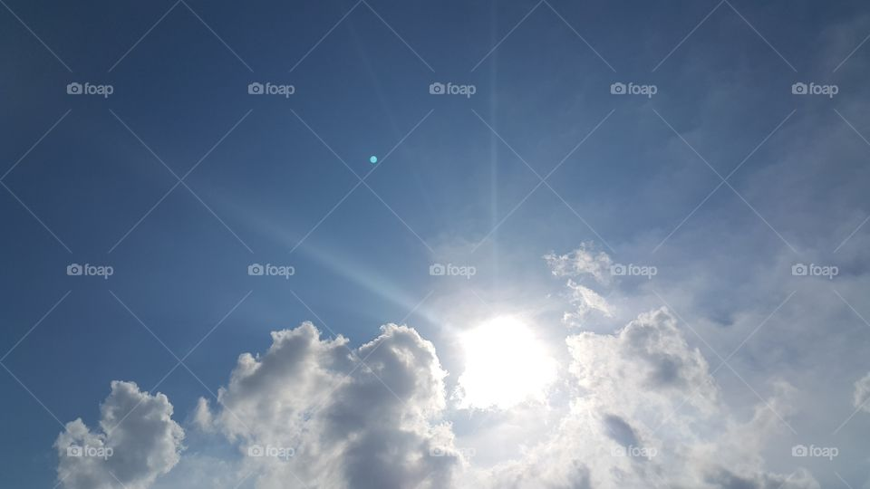 Bright sun with rays on blue sky with clouds