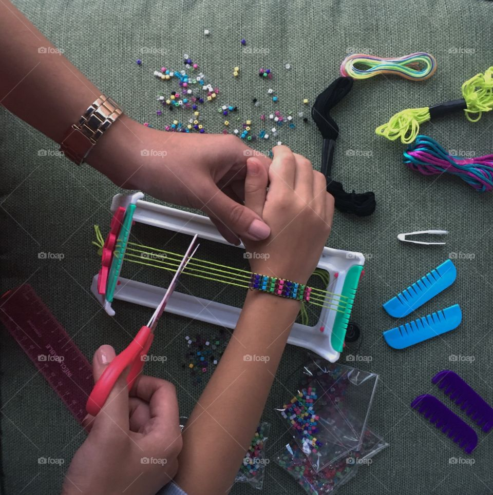 Creativity runs in the genes. Older sister is spending quality time with her younger sister, making bracelets together!