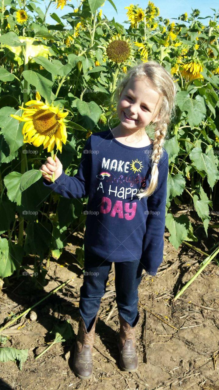 Happy little girl in sunflower field