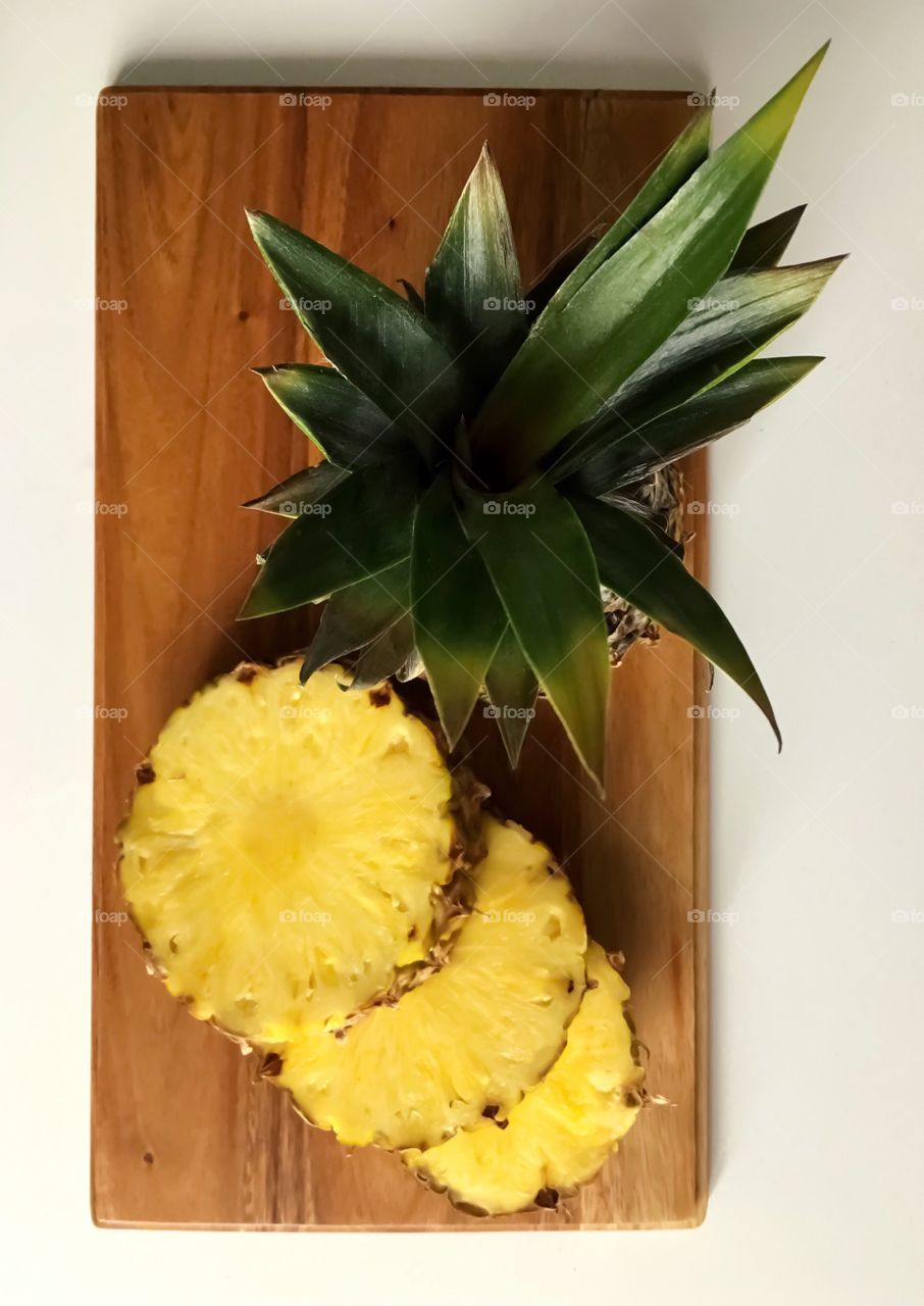 SweetJuicyFresh Pineapple/ on the cutting board. Bright colors make fruit more desirable.