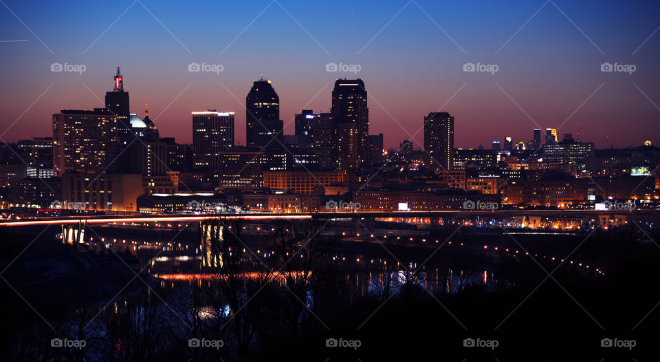 Downtown Saint Paul shines on a hill above the Mississippi River with the Minneapolis skyline visible in the background. Saint Paul, Minnesota.