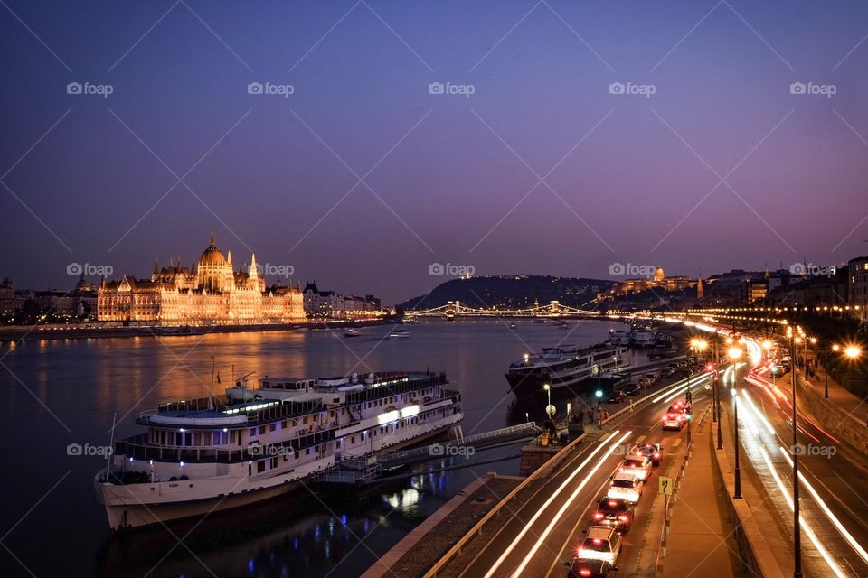 Fine evening in Hungary's Budapest with the scenery of the Hungarian Parliament Building, Danube River, cruises, boats, and city traffic