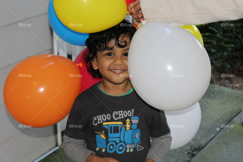 Smiling boy sitting with balloon