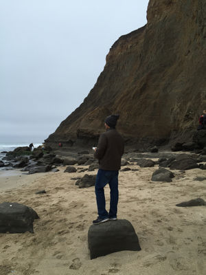 Man standing on a rock on the beach