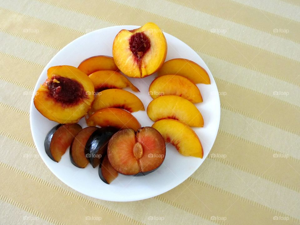 Halved and sliced plum, nectarine and peach