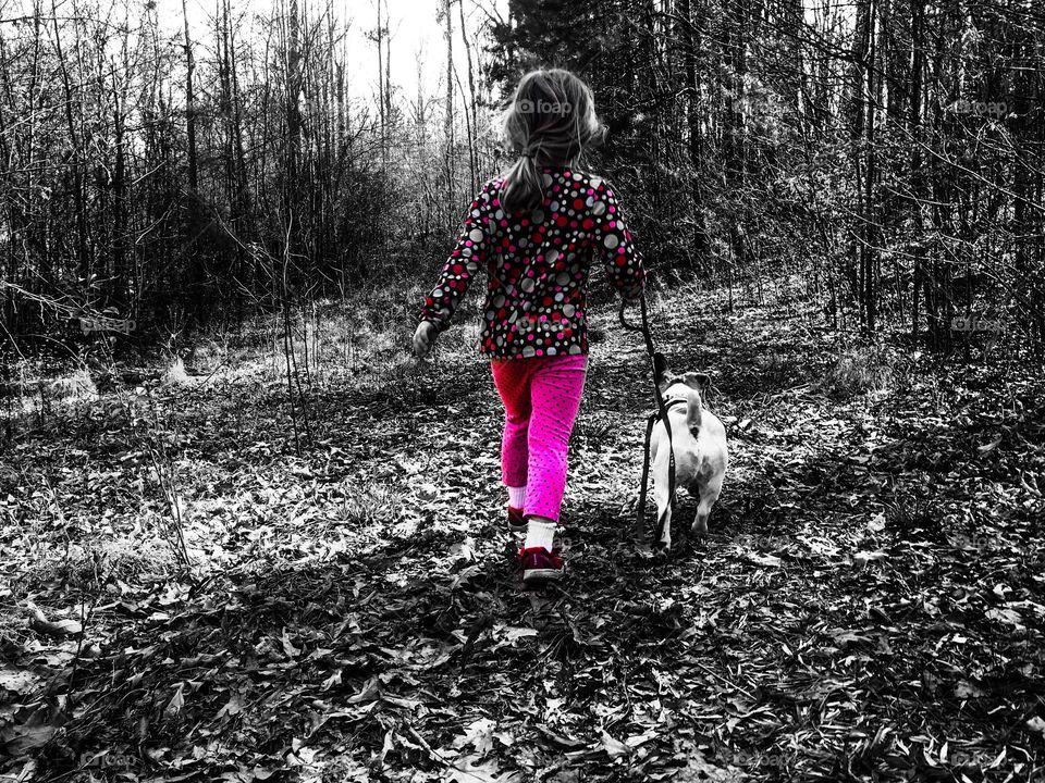 Color pop or color splash of a sweet little girl walking her dog in the forest.
