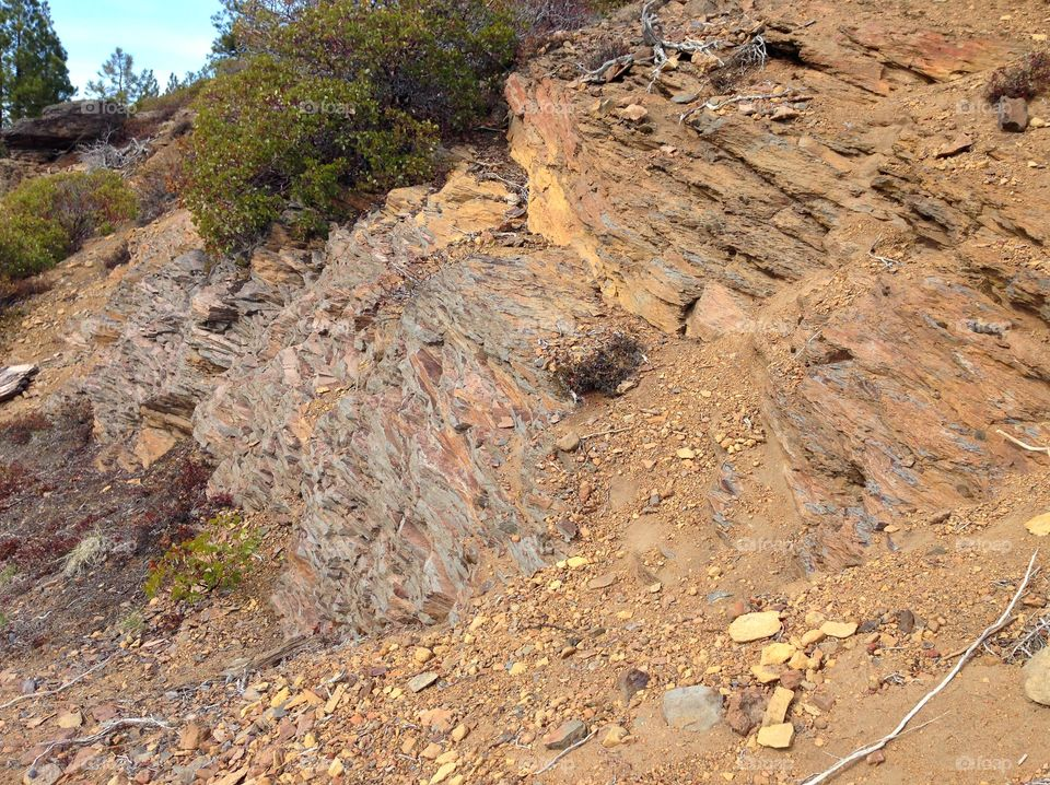 Rough layers of beautiful reddish brown rock and manzanita bushes on a hillside in Central Oregon on a sunny day.