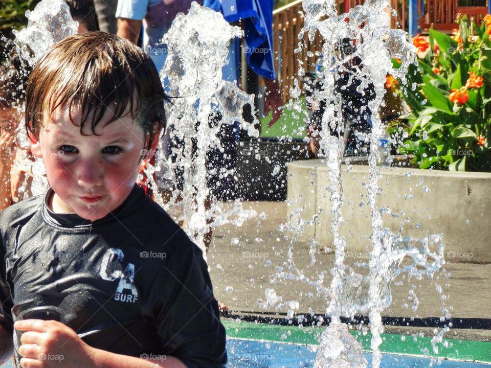 Boy In A Water Fountain. Summertime Fun