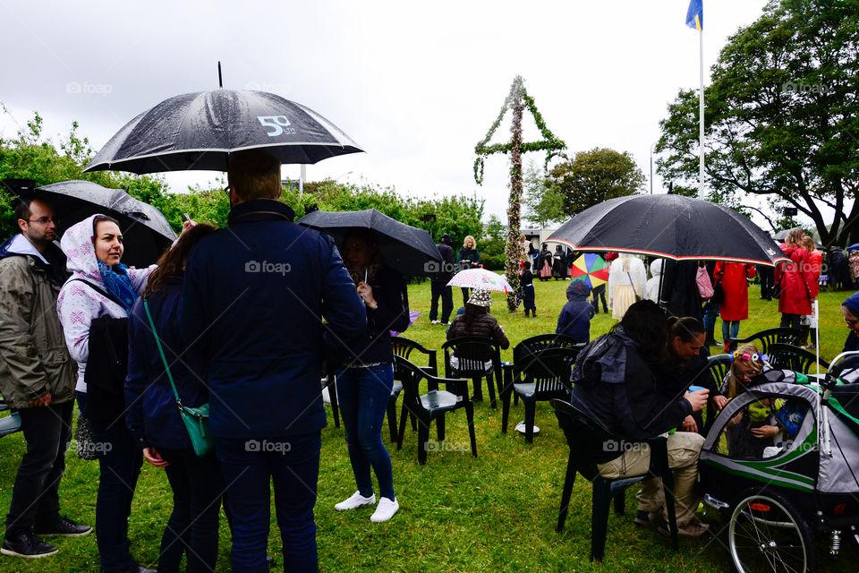 Swedish people is celebrating midsummer in the rain.